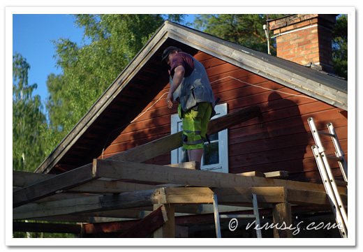 måttar med en bräda och diskuterar lutningen på taket